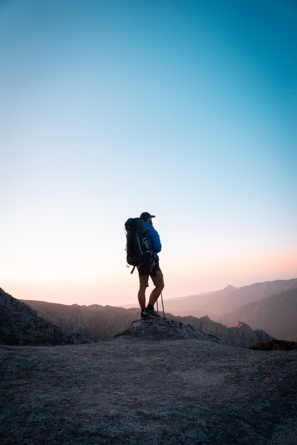 man in black jacket and blue denim shorts with black hiking backpack standing on mountain during
