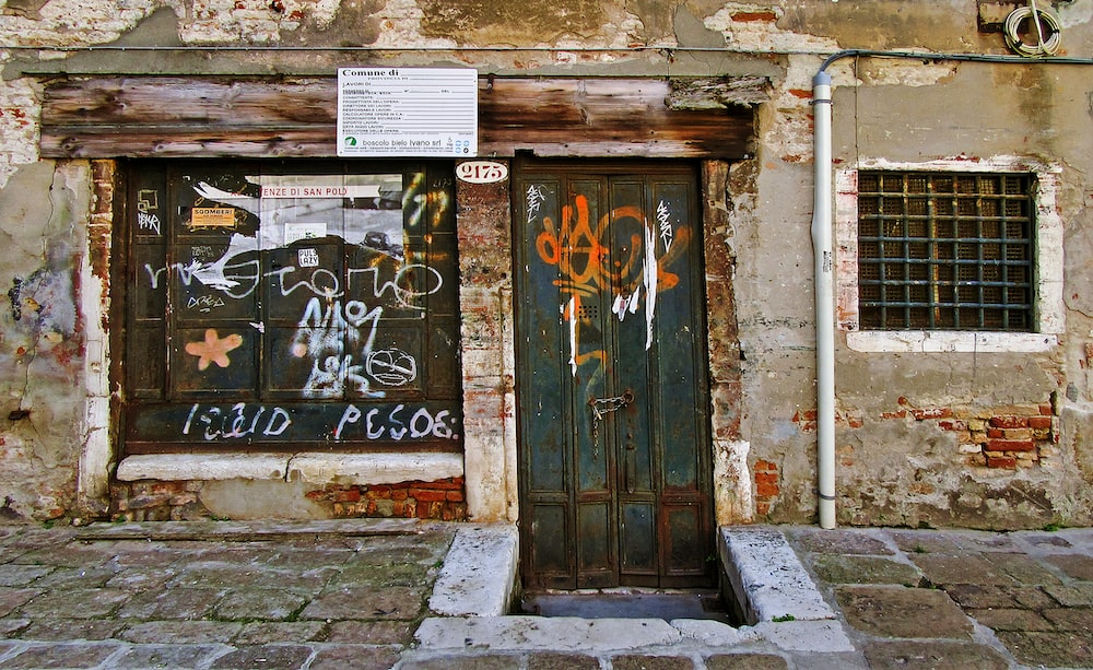 brown wooden door with graffiti
