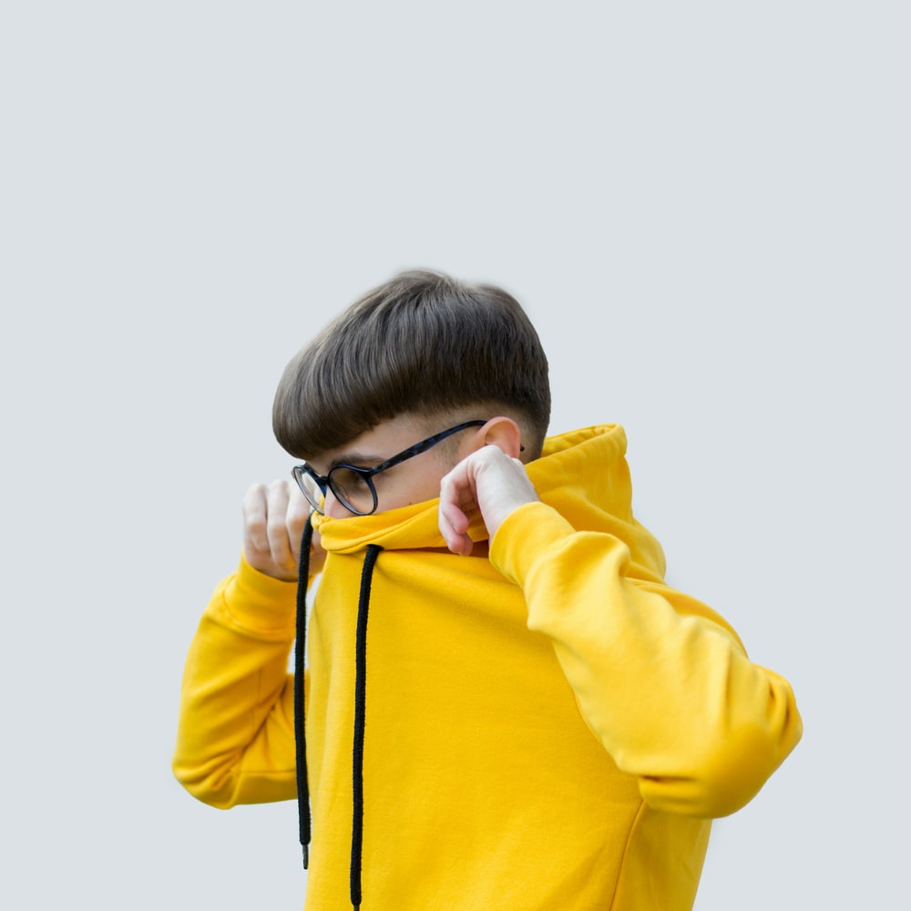 boy in yellow hoodie covering his face