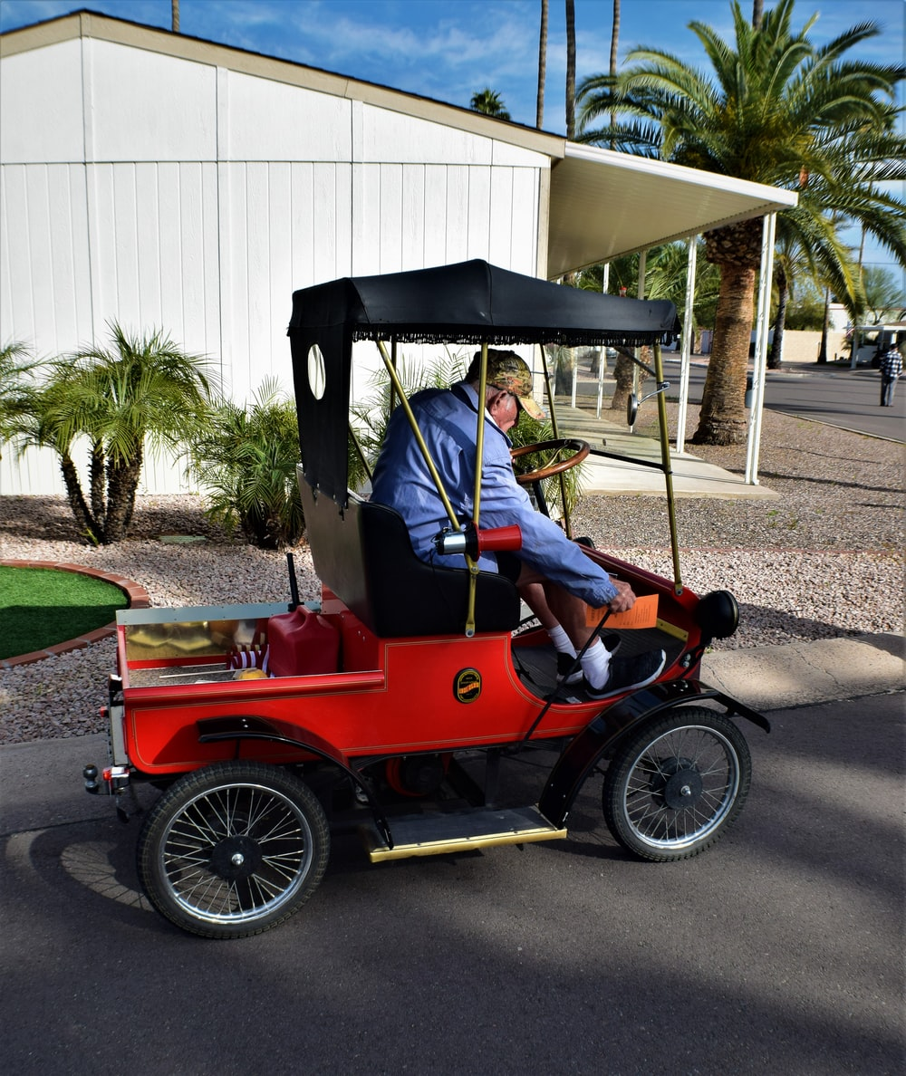 man in blue jacket riding red and black vintage car during daytime