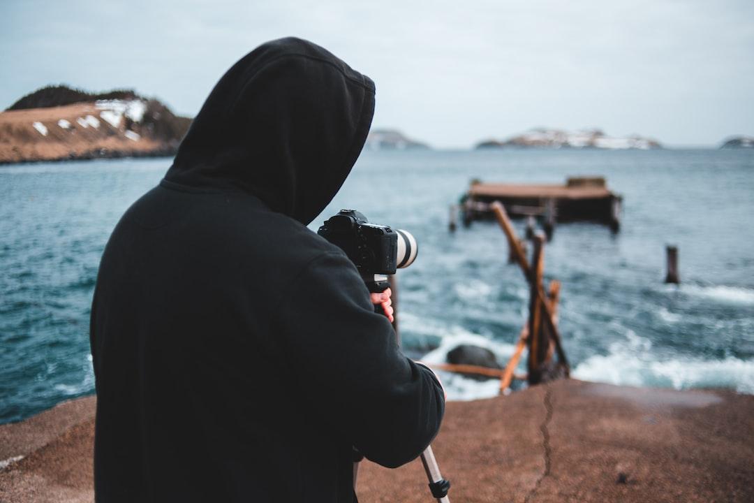 Person In Black Hoodie Holding Black Dslr Camera - unsplash