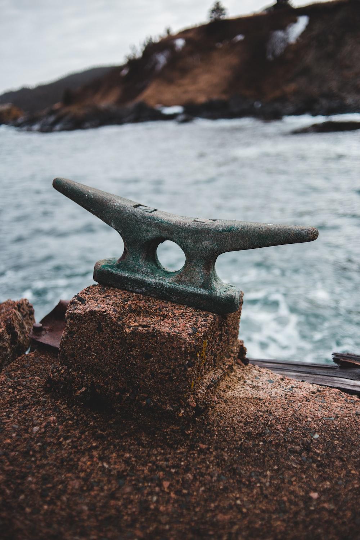 brown metal anchor on brown rock near sea during daytime