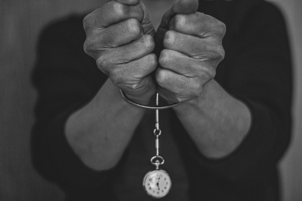 grayscale photo of person holding round pendant necklace