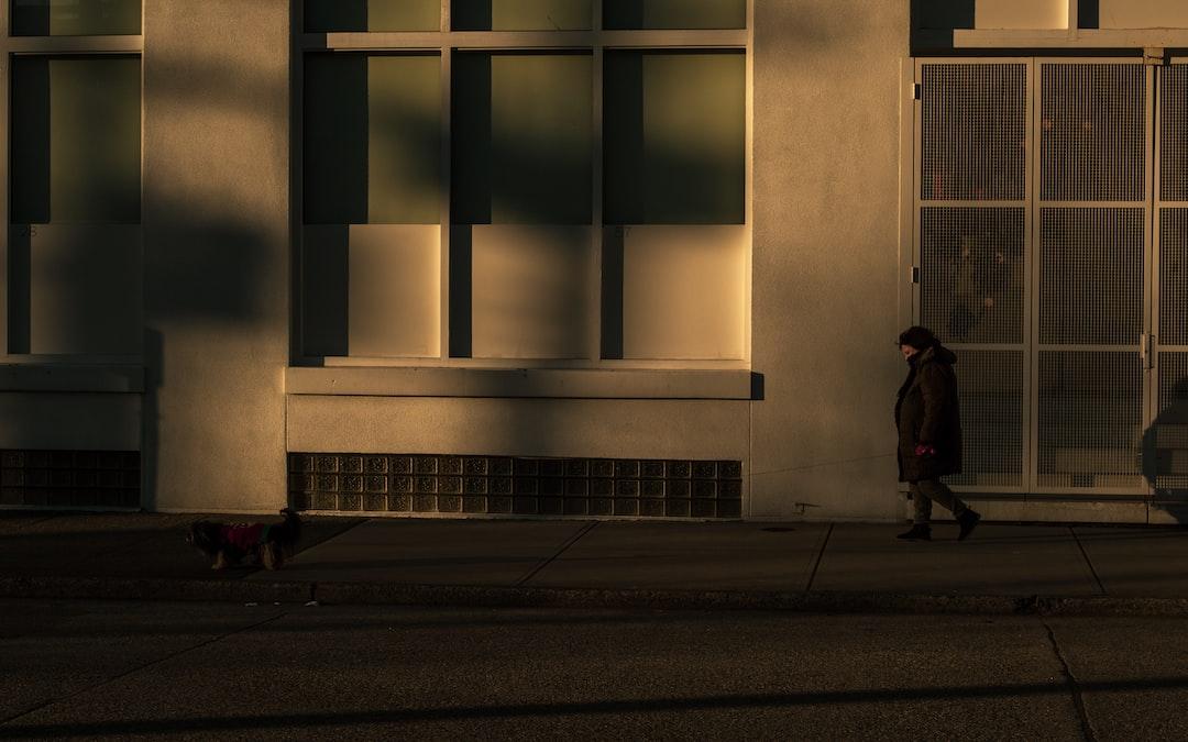 Person In Black Jacket Walking On Sidewalk During Daytime - unsplash