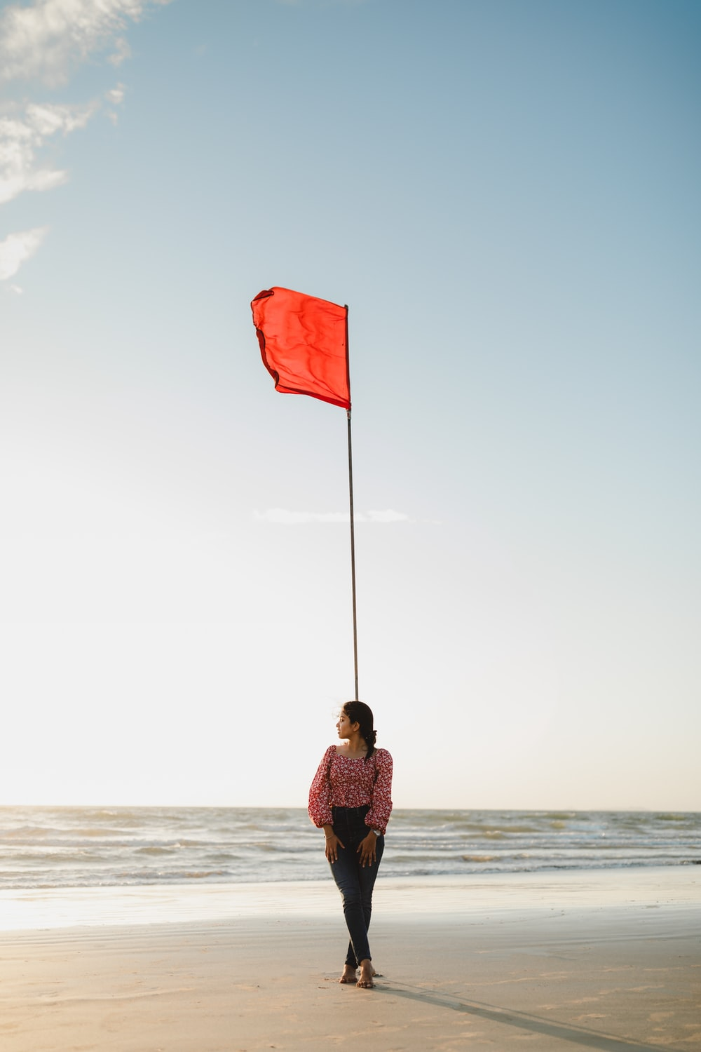 woman in brown jacket holding flag standing on beach shore during daytime