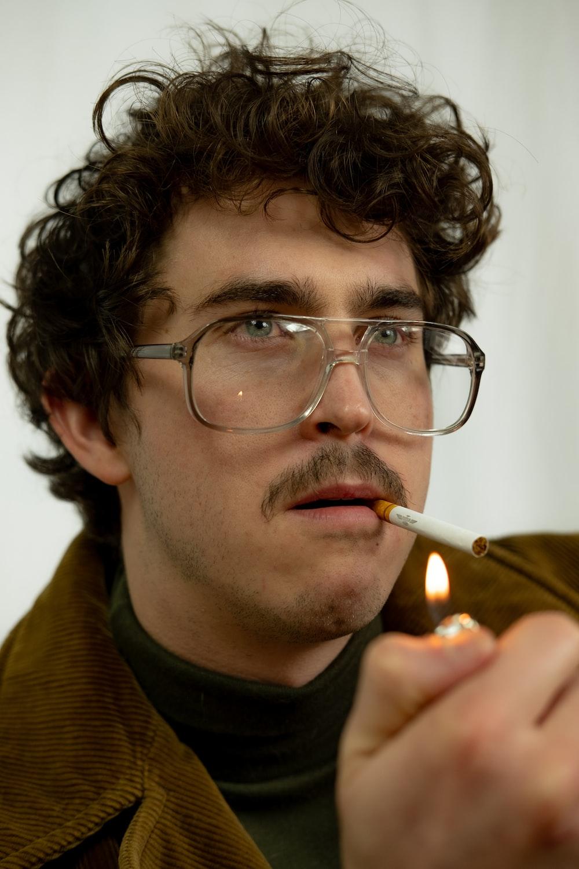 man in green sweater smoking cigarette