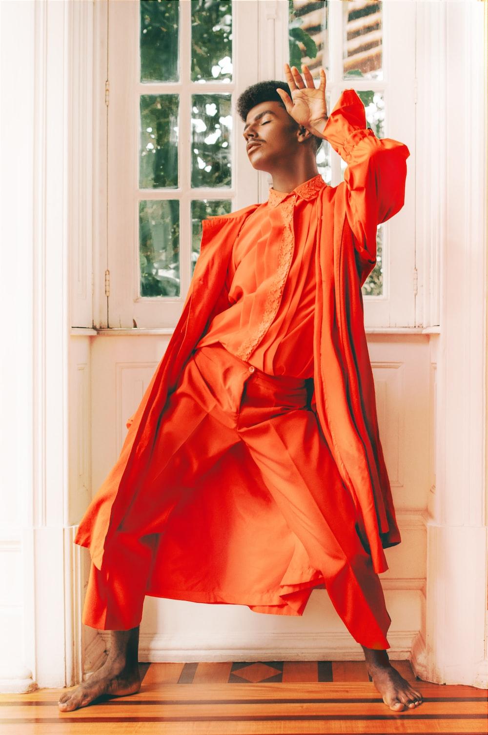 woman in orange long sleeve dress standing near window