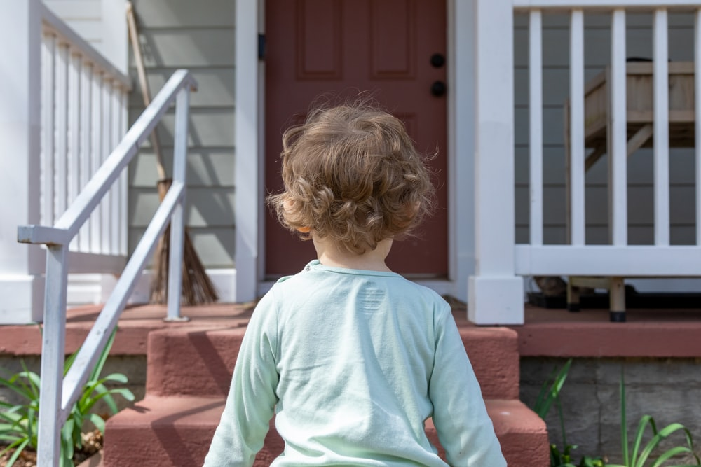 girl in teal long sleeve shirt standing on brown wooden stairs during daytime