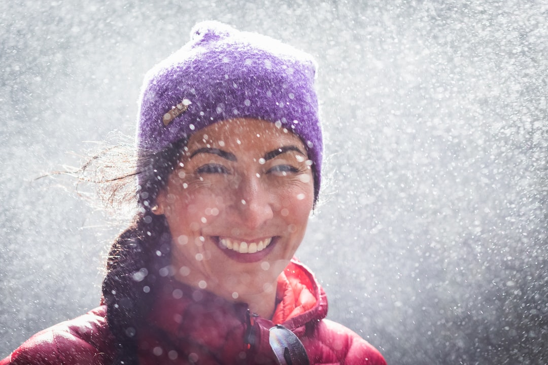 woman smiling and happy in waterfall spray wearing toque