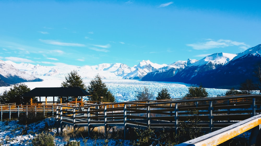 brown wooden fence on green grass field near snow covered mountain during daytime