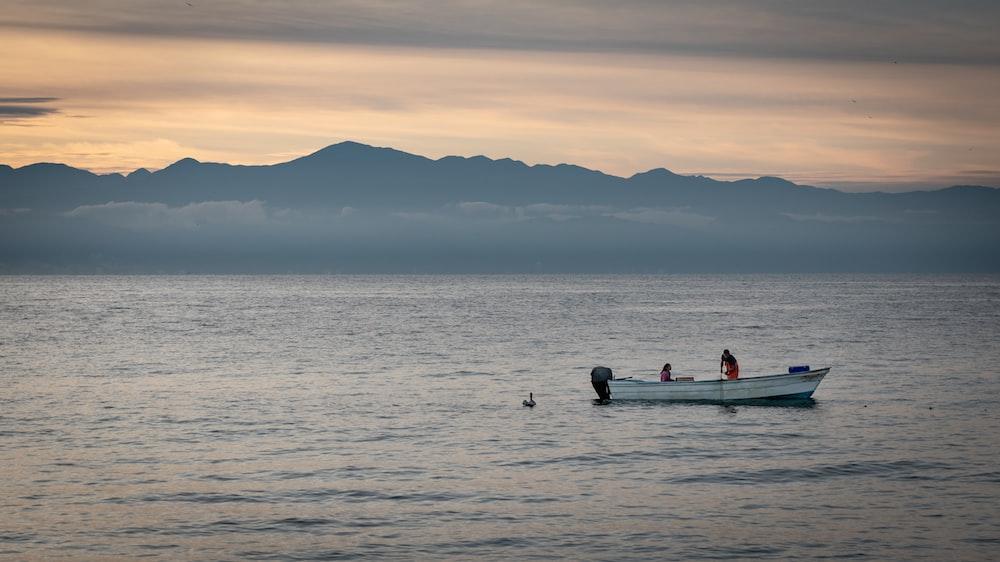 2 people riding on kayak on sea during sunset