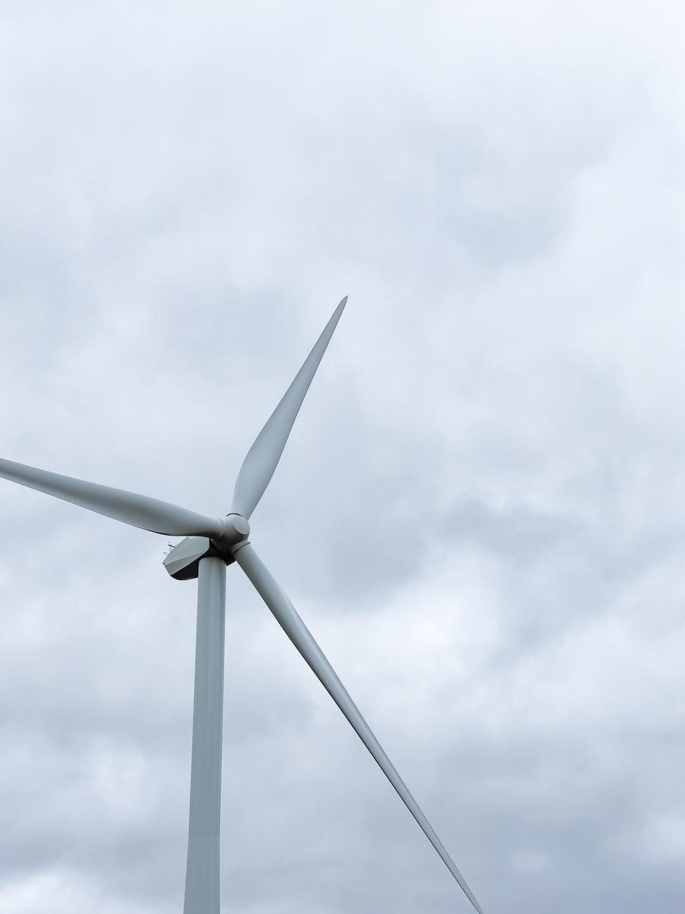 white wind turbine under white clouds during daytime