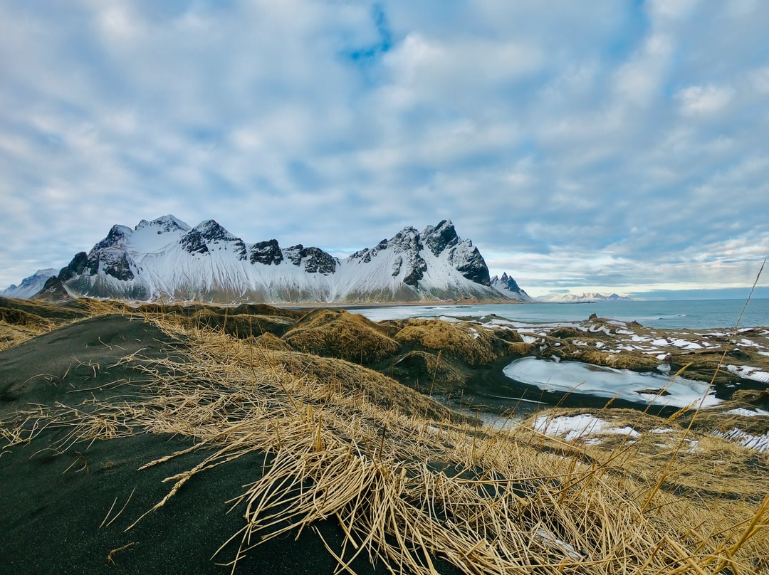 Snow Covered Mountain Near Body of Water Under Cloudy Sky During Daytime - unsplash