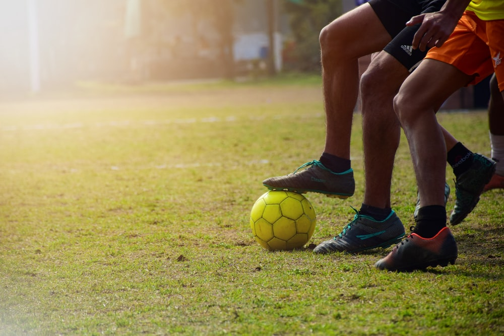 man in black shorts and black nike soccer ball on green grass field during daytime