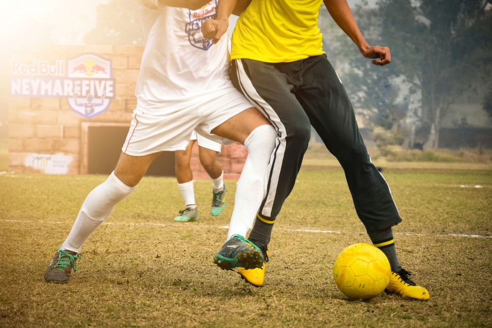 man in yellow shirt and black pants playing soccer