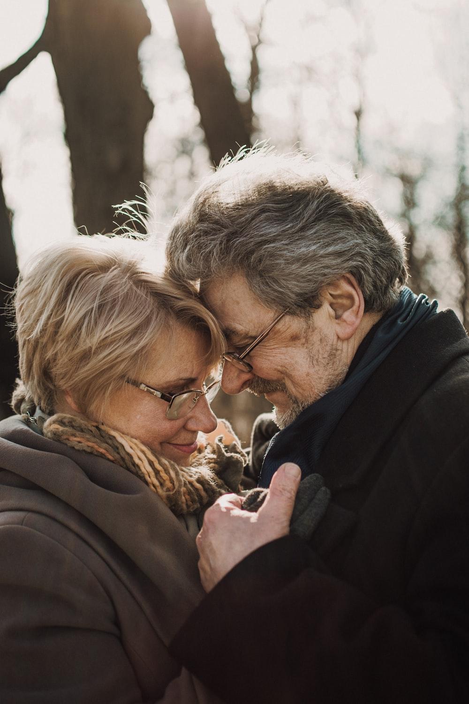 man in black jacket kissing woman in brown coat