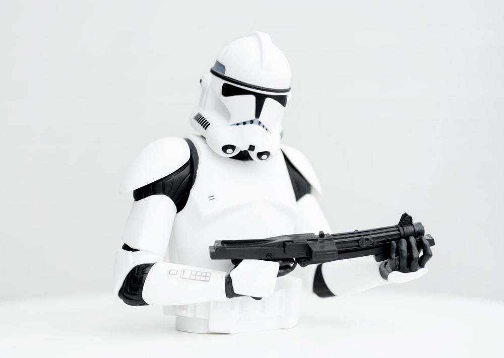 white robot holding black airsoft rifle