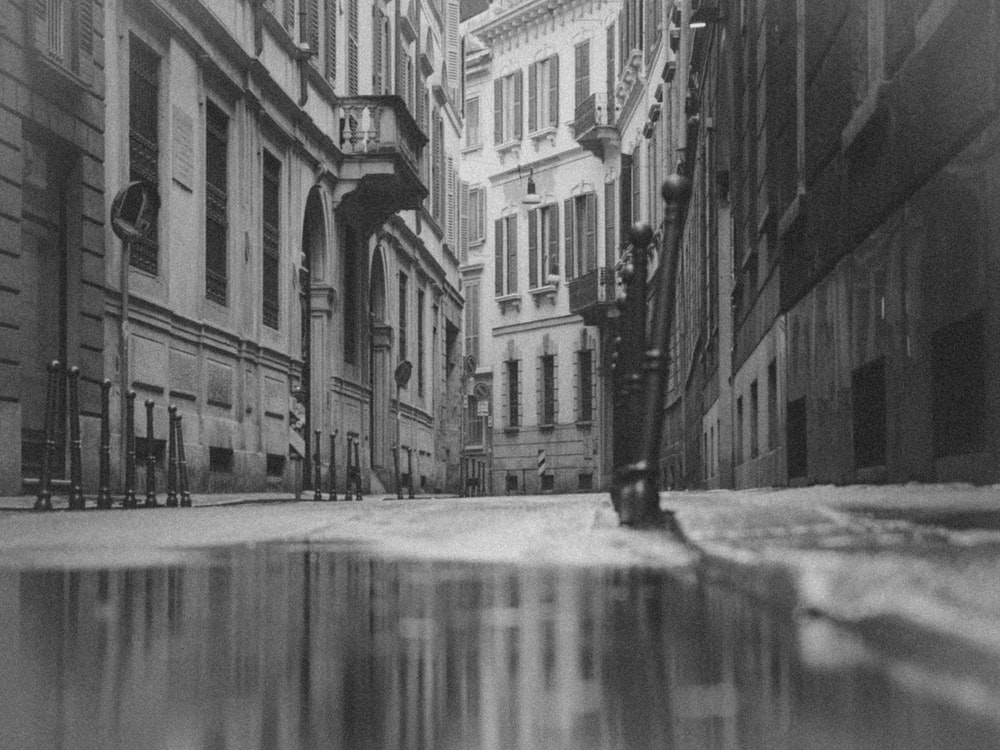 grayscale photo of a street in between buildings