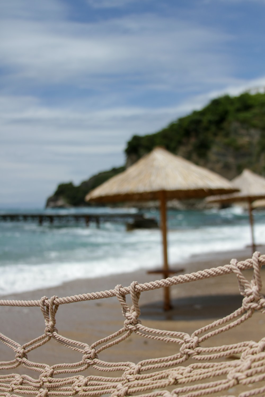 brown wooden beach umbrellas on beach during daytime