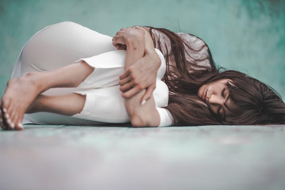 woman in white shirt lying on blue floor