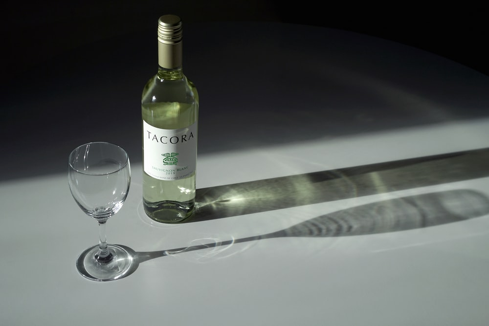white labeled bottle beside wine glass on table