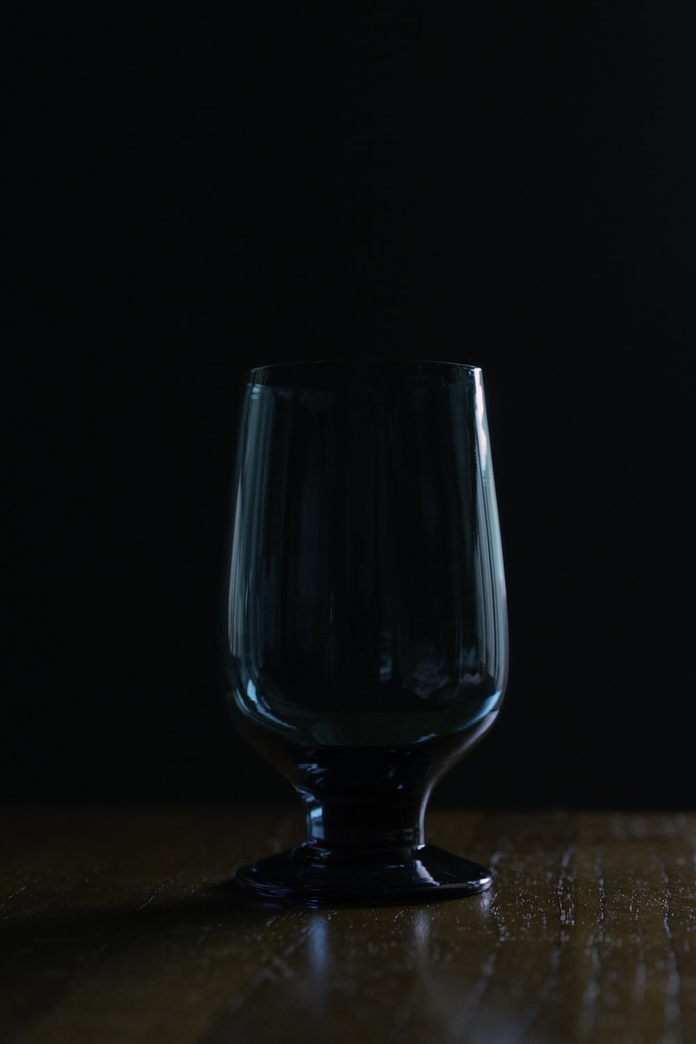 blue drinking glass on brown wooden table