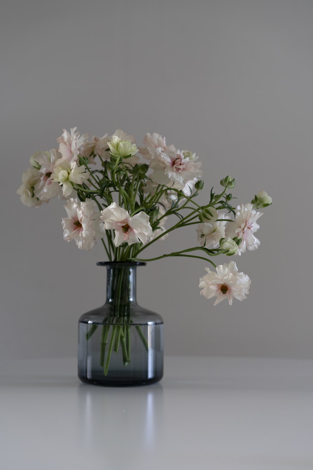 white and pink flowers in blue glass vase