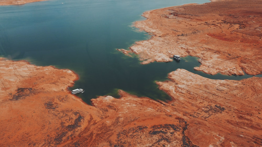 aerial view of brown land near body of water during daytime