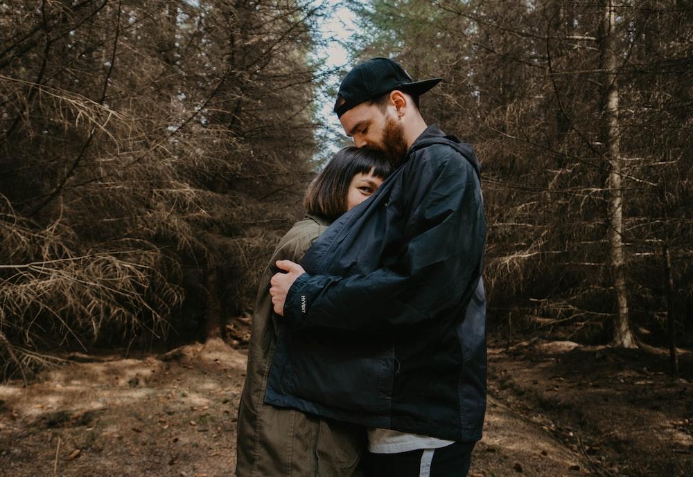man in black jacket hugging woman in black jacket