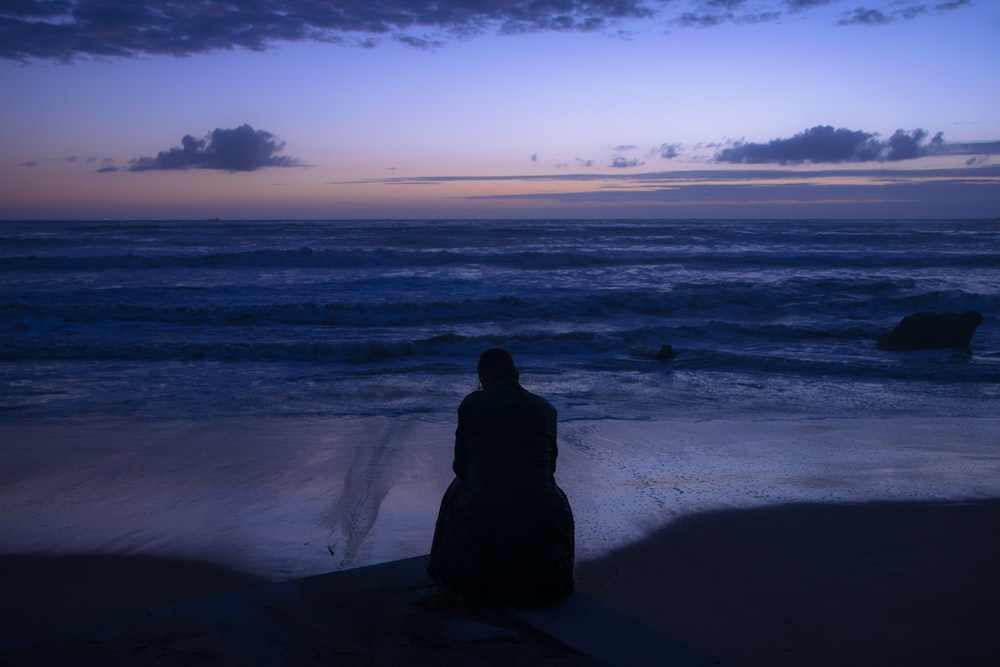 silhouette of person sitting on seashore during sunset