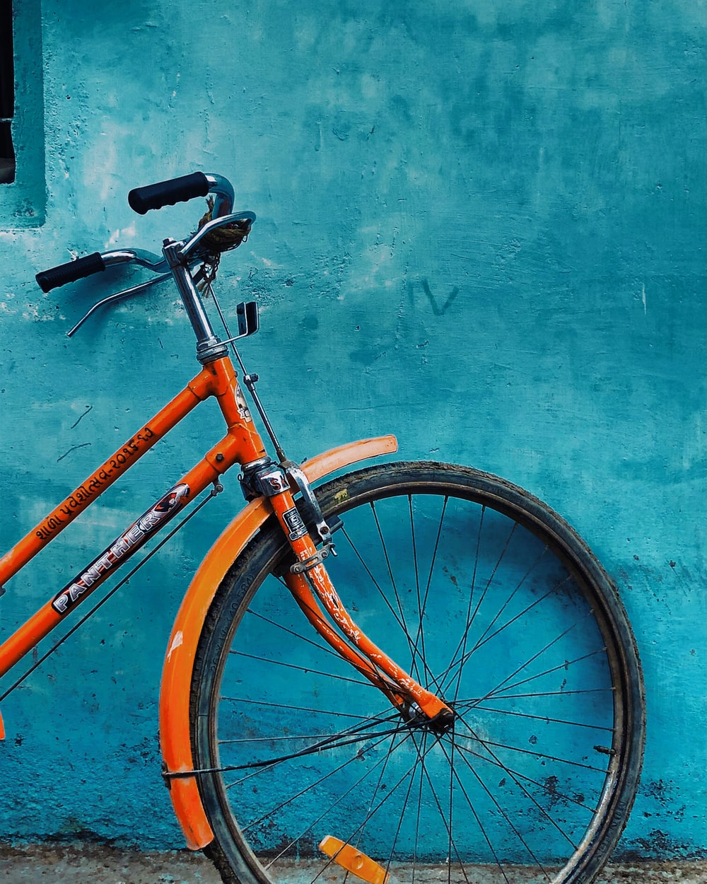 orange and black bicycle leaning on blue painted wall