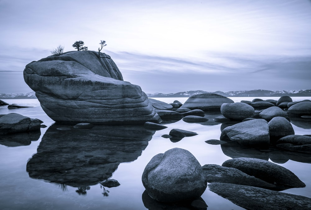 gray rock formation on body of water during daytime