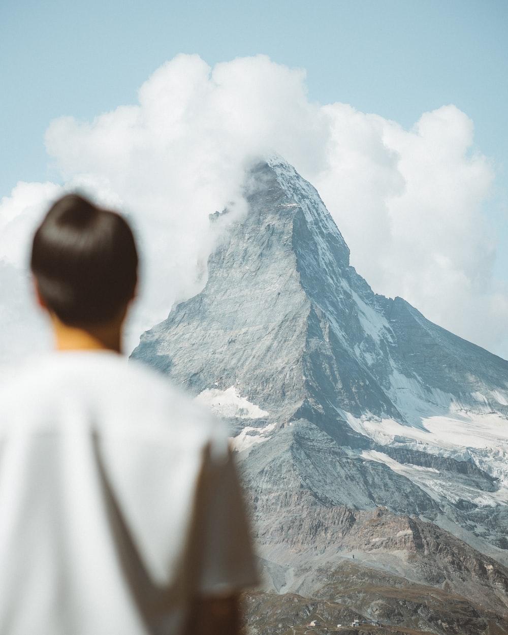 man in white shirt looking at mountain