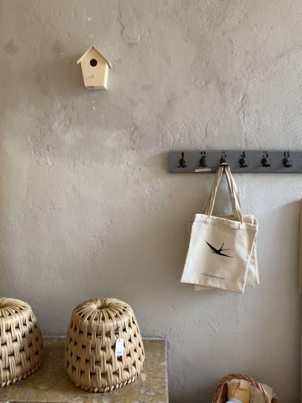 white leather tote bag hanged on white wall