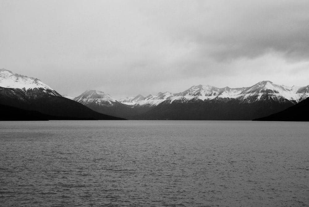 grayscale photo of mountains near body of water