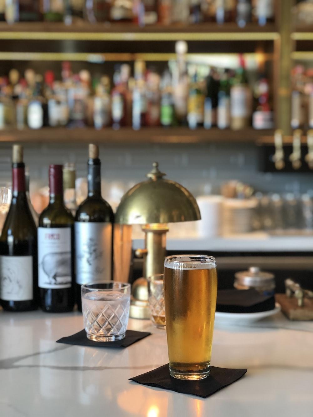clear drinking glass beside wine bottle on table
