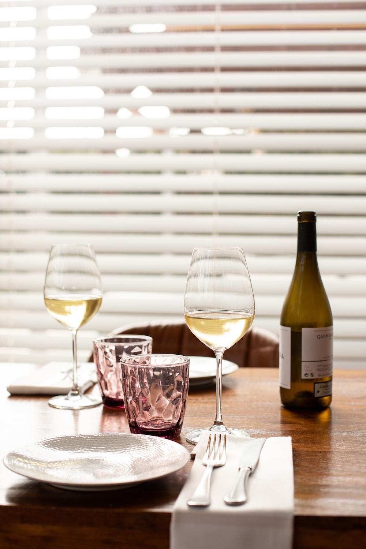 clear wine glass beside wine bottle on table