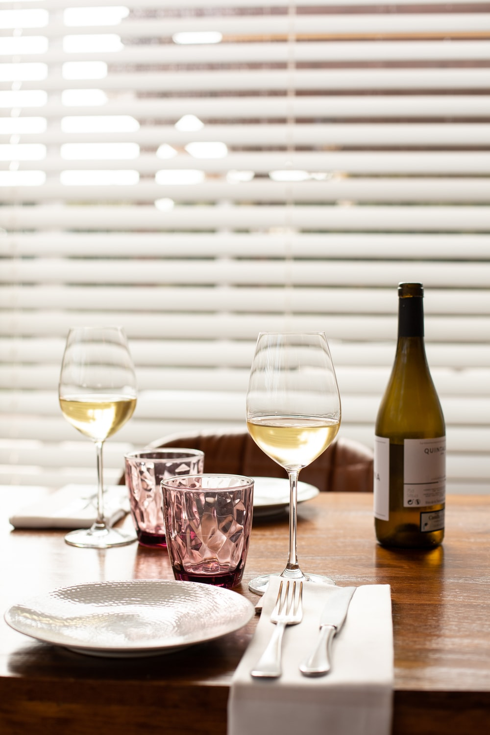clear wine glass beside wine bottle on table