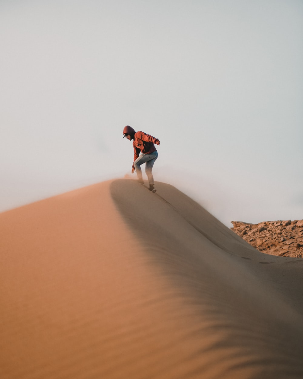man in red jacket and white pants walking on sand dunes during daytime