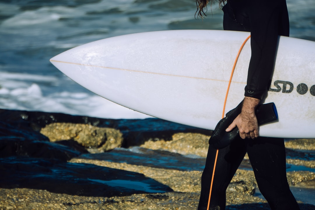 Surfer holding his board, standing on rocks.