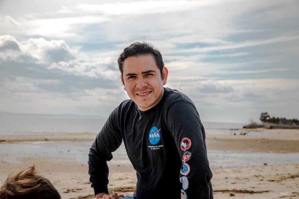 boy in black hoodie standing on brown sand during daytime