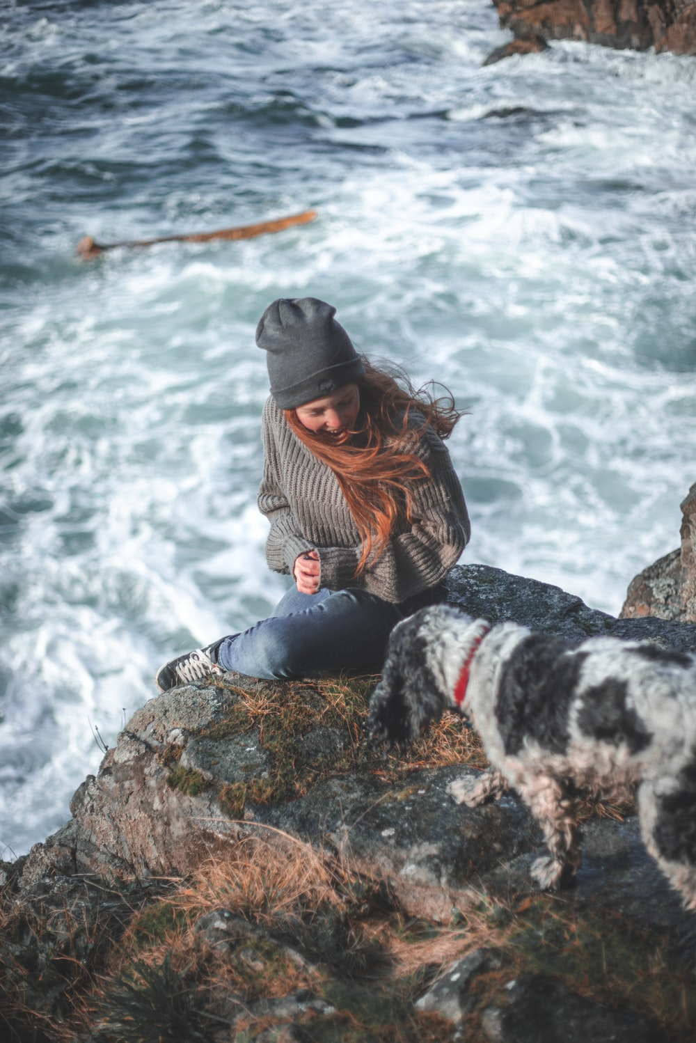 woman in gray sweater and black pants sitting on rock by the sea during daytime