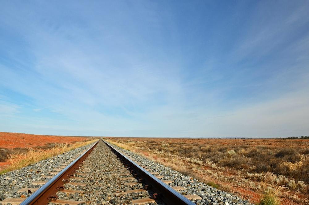 black train rail under blue sky during daytime