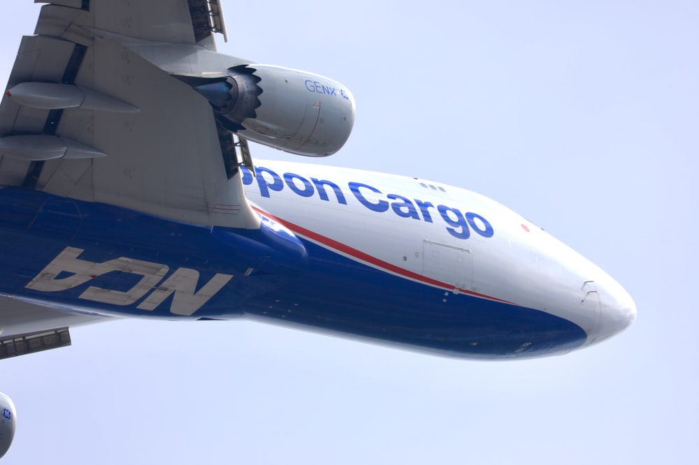 white and blue airplane under white sky during daytime