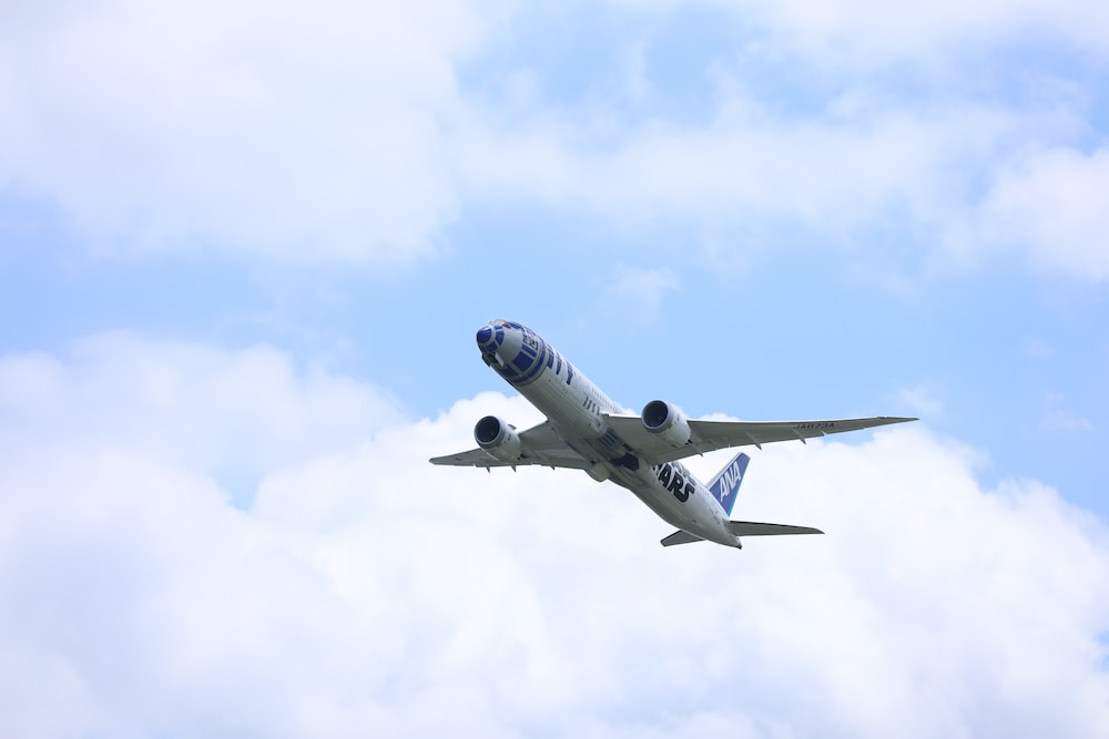 white and blue airplane in the sky