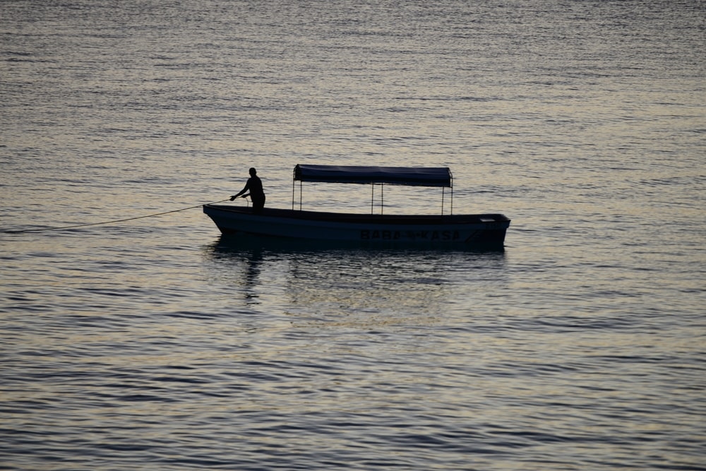 man in blue boat on sea during daytime