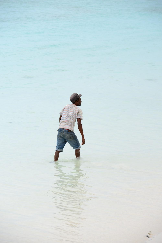 man in white t-shirt and blue denim shorts walking on beach during daytime