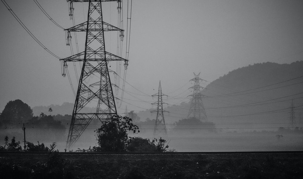 grayscale photo of electric towers