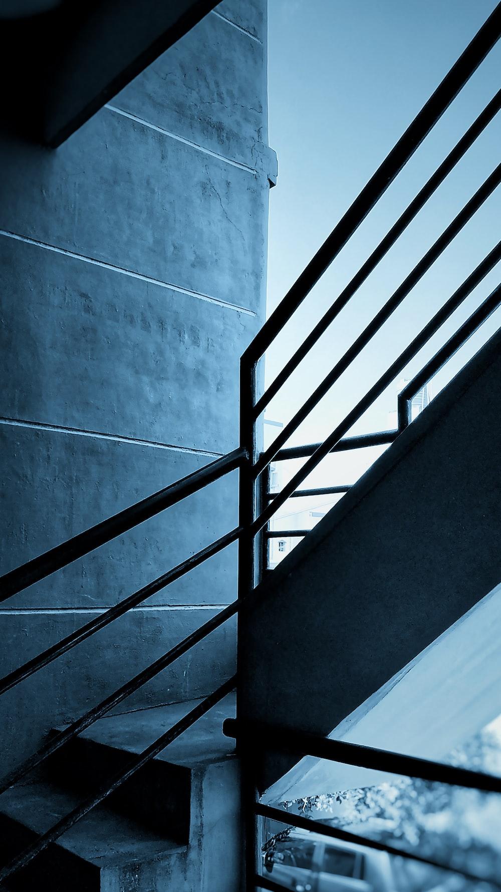 black metal staircase on gray concrete wall