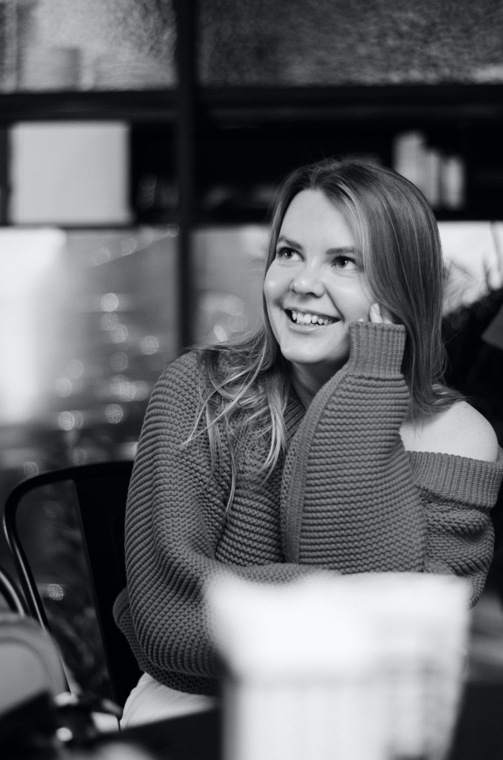 grayscale photo of woman in sweater smiling